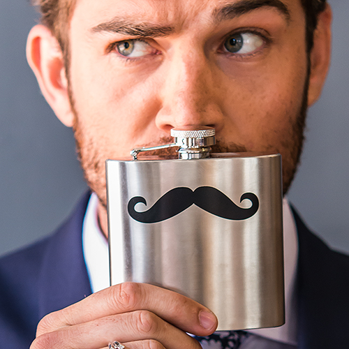 Groom holding a mustache flask