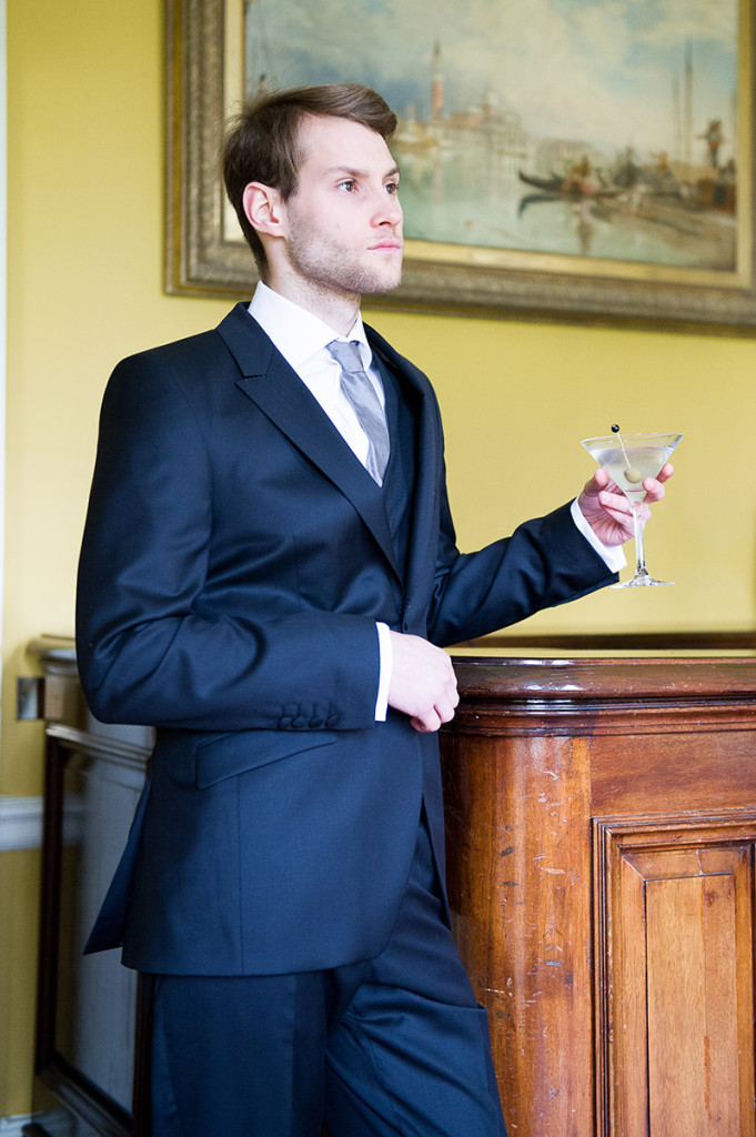 Groom wearing a blue suit with a drink