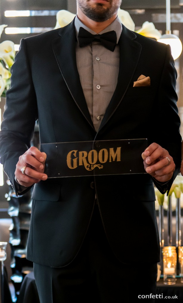 Groom in black Art Deco theme with sign