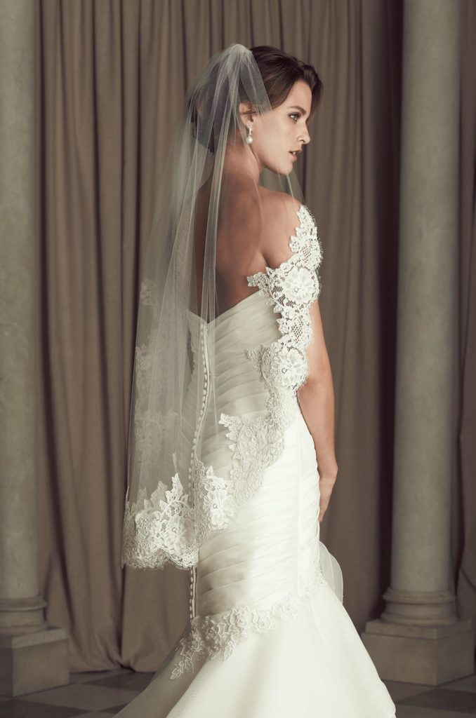model posing in lace wedding dress and chapel length veil all by Paloma Blanca