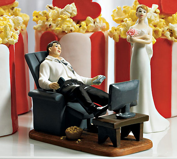 Cake topper with groom lounging, watching television