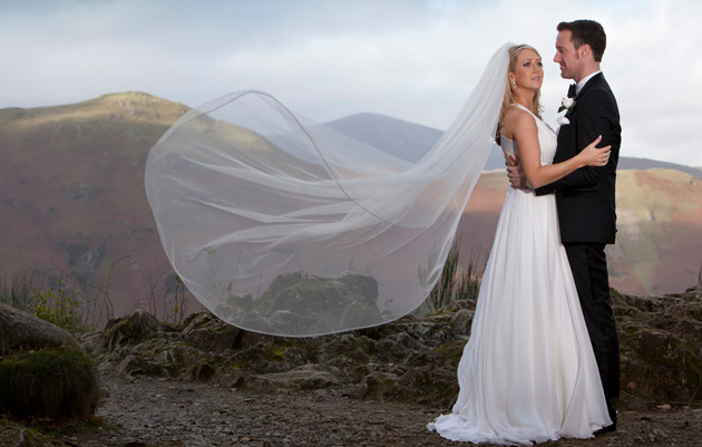 Bride and Groom on a hill with wedding veil caught in the wind