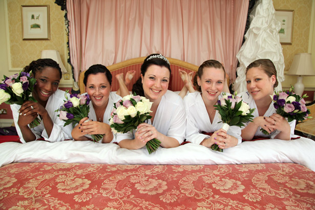 Bride with bridesmaids holding white and lavender bouquets