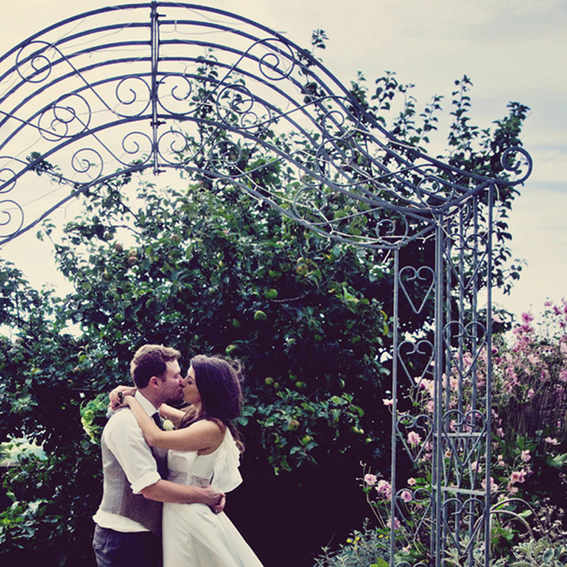 Bride and groom embrace in front of intricate metal arch