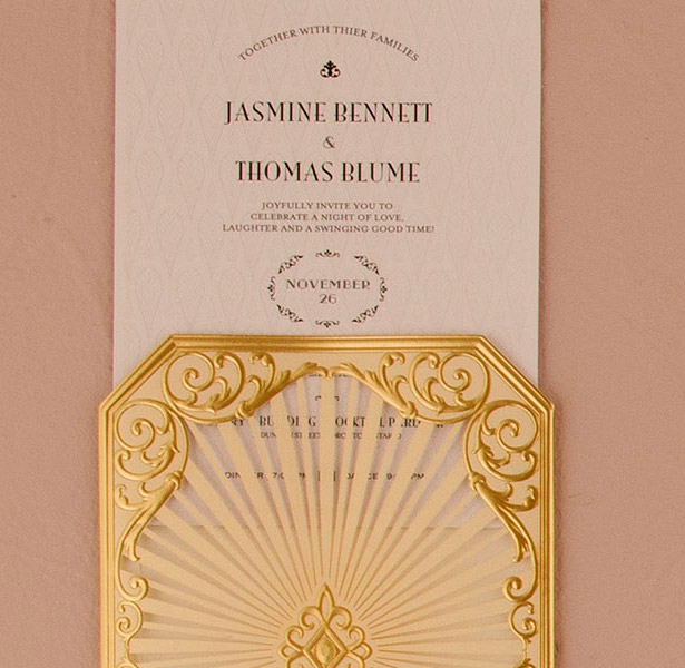 Cream and gold decorated wedding invitation close-up