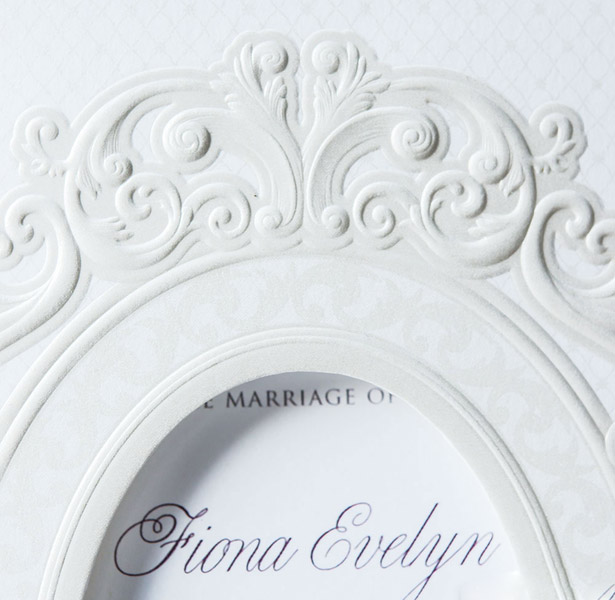 White laser decorated wedding invitation close-up