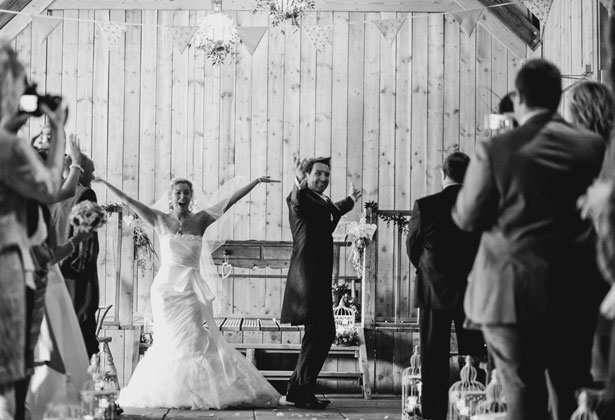 Bride and groom dancing down the aisle