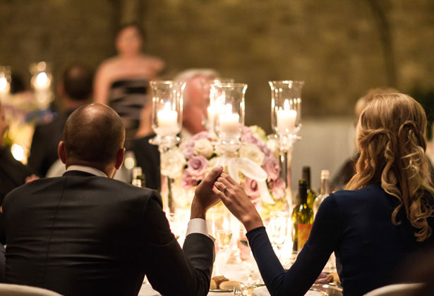 The bride and groom holding hands at the top table