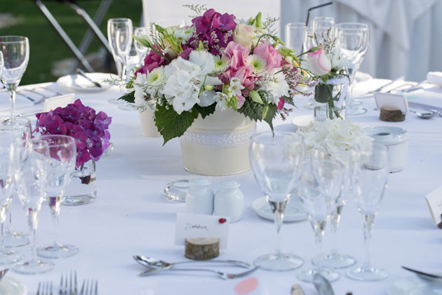 Pink and white wedding centrepiece with white table setting