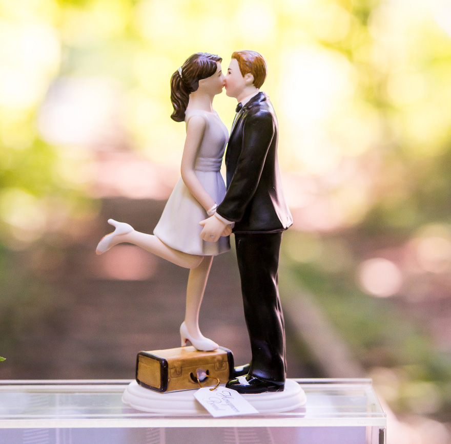 """A Kiss And We're Off!"" Figurine - Light Skin Tone - Bride Standing on Suitcase to Kiss the Groom - Unique Cake Topper 