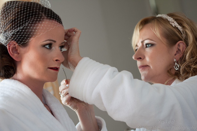 Bridesmaids helping the bride with her hair