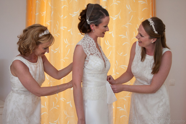 Bridesmaids helping the bride with the final touches to her dress