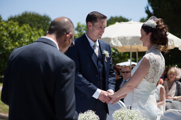 Bride and groom holding hands at the ceremony