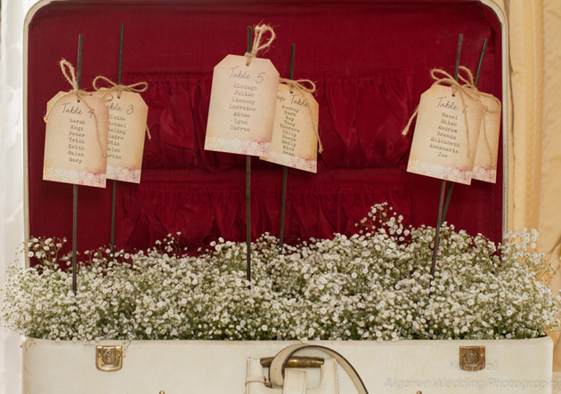 Vintage tag seating plan with baby breaths and vintage suit case
