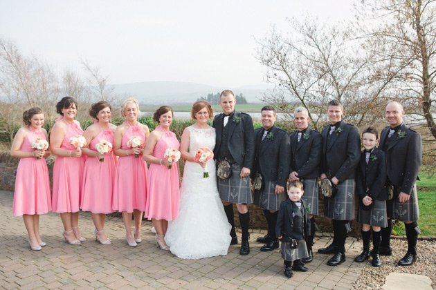 The newlyweds with their bridesmaids in coral pink and their groomsmen in kilts