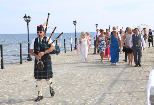 Traditional piper leading the wedding party to the reception