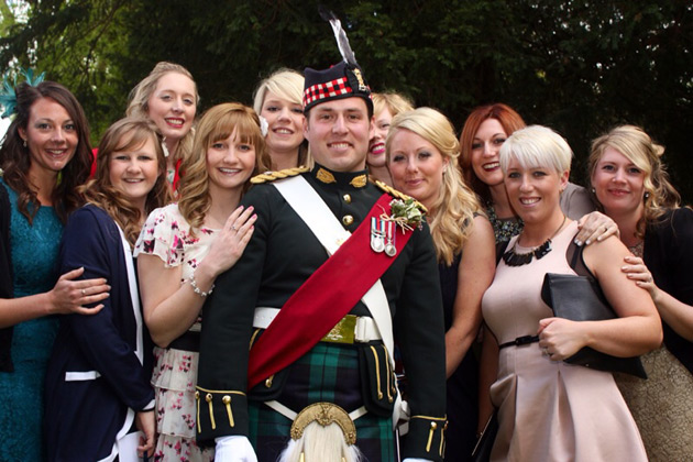 Groom in a military uniform with wedding guests