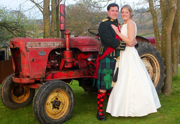 The bride and groom standing next to a red tractor