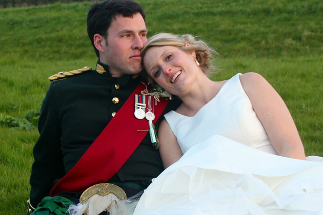 The bride and groom sitting on the grass