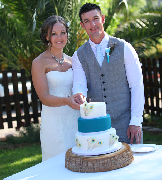 Bride and groomcutting their white and blue peacock feathered wedding cake