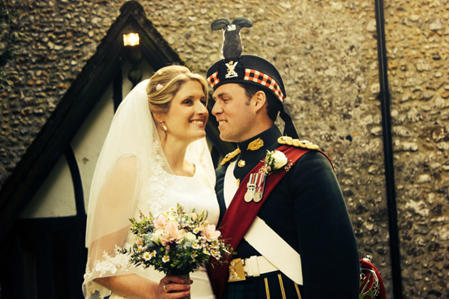 Bride in a lace wedding dress and veil with her groom in military uniform