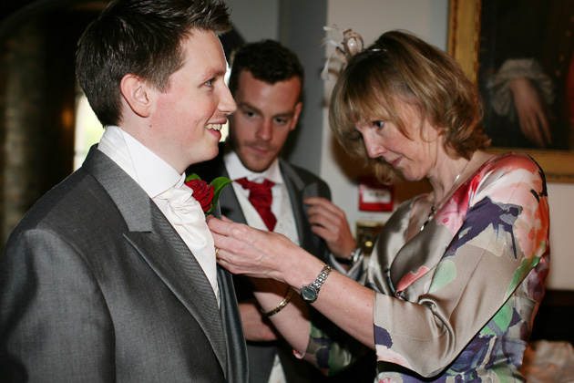 Mother of the groom pinning a red rose button hole on his suit | Confetti.co.uk