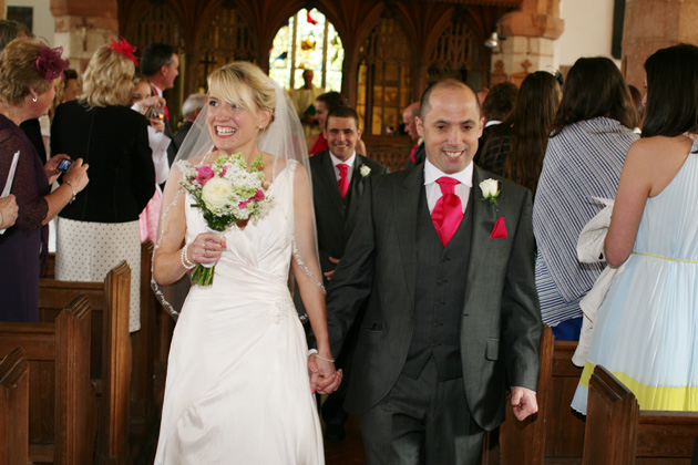 Smiling bride and groom exit the church after the ceremony | Confetti.co.uk
