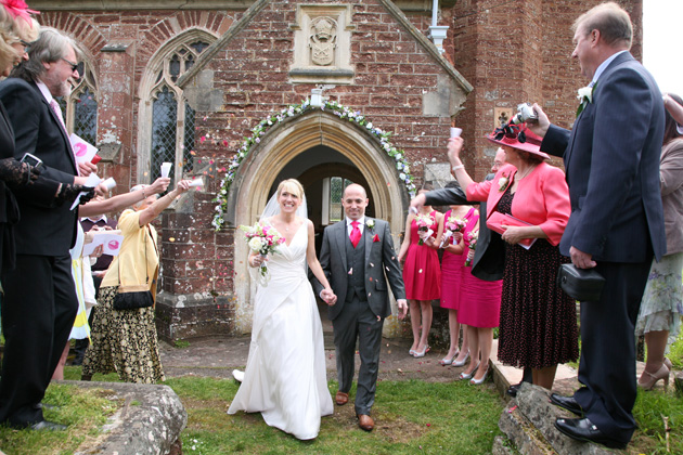 Wedding guests throwing confetti over the newlyweds after the church ceremony | Confetti.co.uk