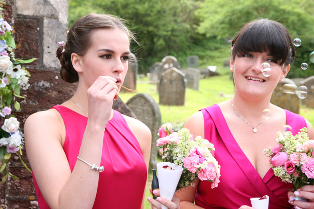 Bridesmaids blowing bubbles after the ceremony | Confetti.co.uk