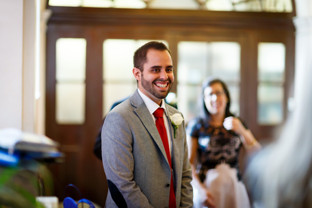 The groom waiting for the bride at the ceremony in a grey suit and red tie | Confetti.co.uk