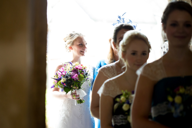 Bride and the bridesmaids walking in to the church | Confetti.co.uk