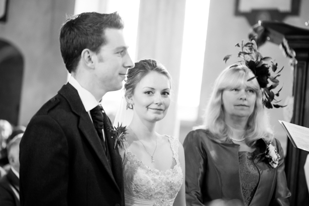 Black and white image of the bride and groom at the alter | Confetti.co.uk