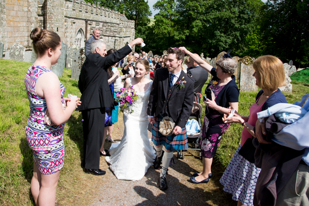 Wedding guests throwing confetti over the newlyweds | Confetti.co.uk