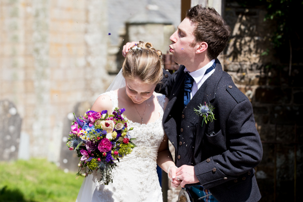 Groom blowing confetti of the brides hair | Confetti.co.uk