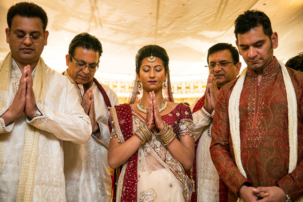 Bride with her family in a traditional Indian bridal outfit praying | Hindu wedding ceremony | Confetti.co.uk