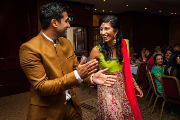 The bride in her traditional Indian outfit and the groom in a brown suit by Zara entering their Indian Reception | Indian wedding reception ideas| Confetti.co.uk