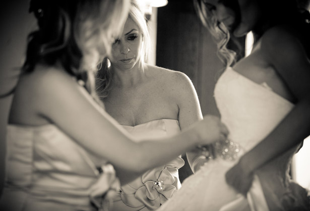 How to Choose Your Bridesmaids | Bridesmaids helping the bride with her detailed belt | Confetti.co.uk