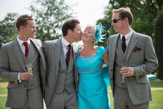 Mother of the Groom Wedding Duties |Image courtesy of King & Allen | Mother of the groom in a blue dress and feathered fascinator with the son and groomsmen | Confetti.co.uk