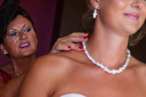 Mother of the Bride Wedding Duties | Image courtesy of Yes I do! Algarve Wedding Photography|Bride putting the brides pearl necklace on for her | Mother of the bride and bride moments | Confetti.co.uk