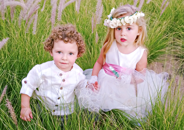 Adorable page boy and flower girl in the grass | Confetti.co.uk
