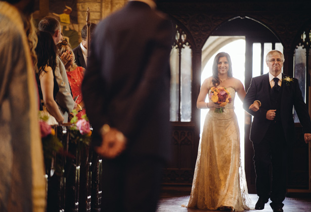 Bride in her gold dress walking down the aisle with her father | Francesca & Arun's Fusion Real Wedding | Confetti.co.uk