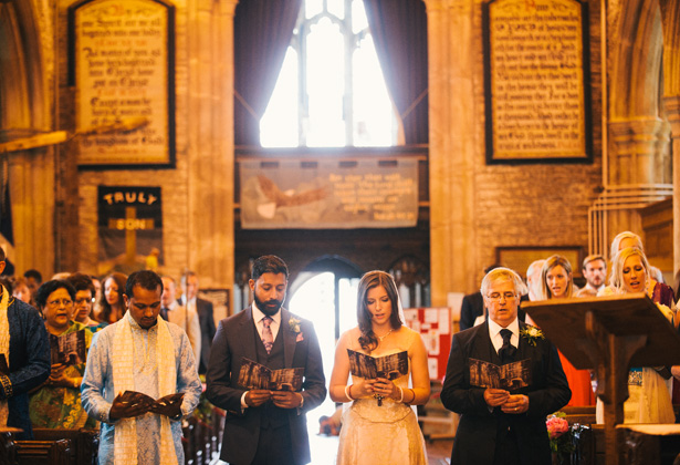 The bride and groom together at the altar singing hymns | Francesca & Arun's Fusion Real Wedding | Confetti.co.uk