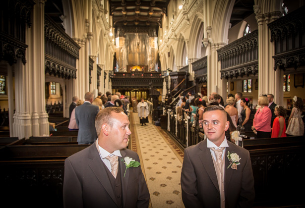 Groom and the best man waiting at the altar in the St. Michael and all Angels' church in Ashton | Becki and Rob's Real Wedding By Jenny Martin Photography | Confetti.co.uk
