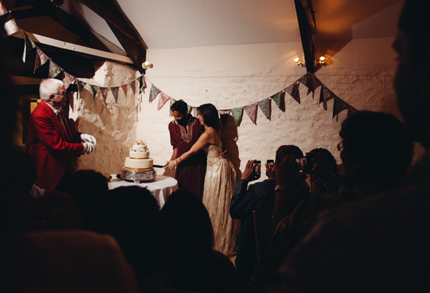 Bride and groom cutting their 3 tier wedding cake in front of their wedding guests | Francesca & Arun's Fusion Real Wedding | Confetti.co.uk
