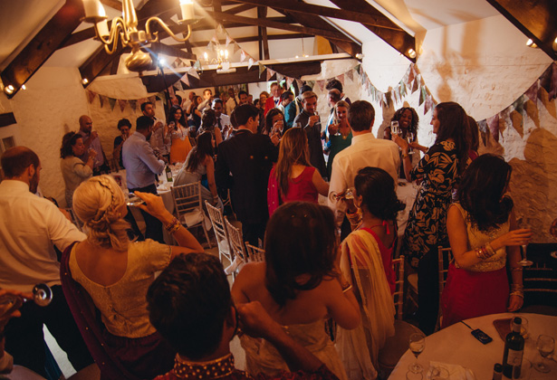 Wedding guests on their feet toasting the newlyweds | Francesca & Arun's Fusion Real Wedding | Confetti.co.uk