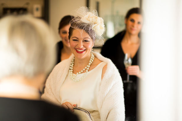Bride ready for her big day | Bride in her white fur shawl, pearls and white vintage inspired dress  | Abigail and Chris's Real Christmas Wedding | Confetti.co.uk