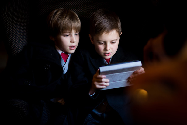 Page boys playing on their Ipad | Abigail and Chris's Real Christmas Wedding | Confetti.co.uk