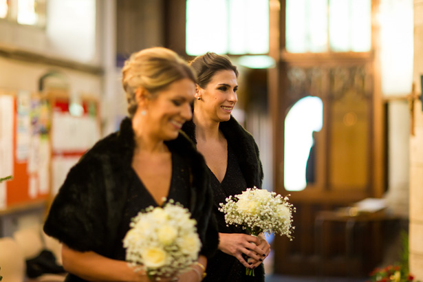 Bridesmaids in black dresses walking down the aisle | Abigail and Chris's Real Christmas Wedding | Confetti.co.uk