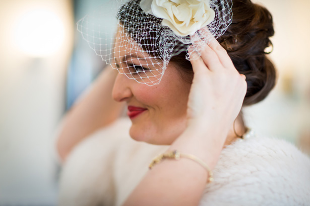 Bride putting the final touches to her attire | White bridal fascinator | Abigail and Chris's Real Christmas Wedding | Confetti.co.uk