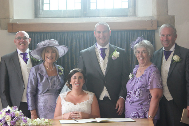Nearly weds signing the register with their family| Purple themed wedding| Rhiannon & Michael's Real Wedding | Confetti.co.uk